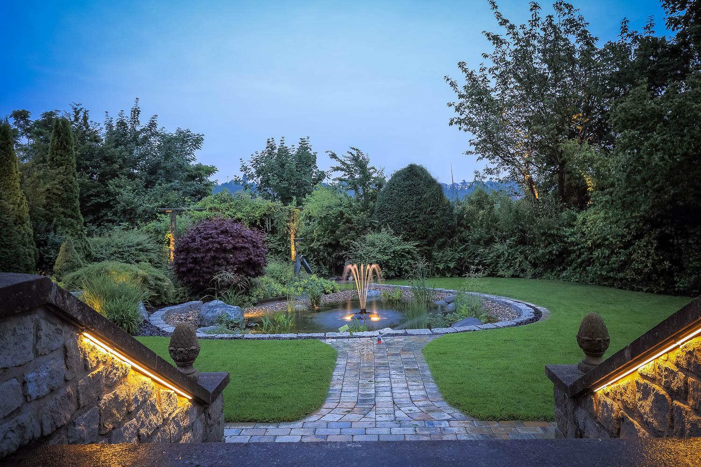 Gartenanlage mit Gartenteich, Gartenweg und Treppe. Beleuchteter Springbrunnen in der Abendstimmung